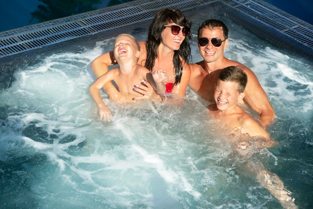 Family of four enjoying a day at the swimming pool together