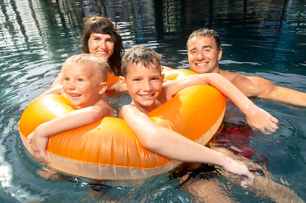 Family of four enjoying a day at the swimming pool together Free Photo