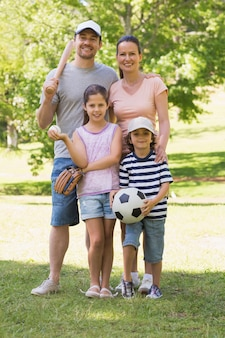 Family of four holding baseball bat and ball in park