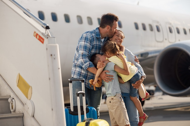 Family of four kissing each other while going on a trip, standing in front of big airplane outdoors. people, traveling, vacation concept
