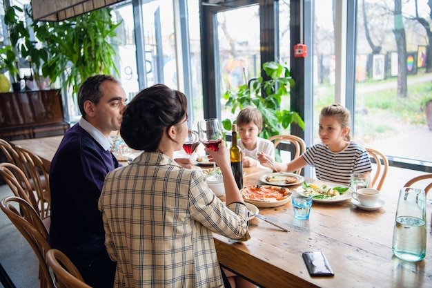 A family of four raising glasses at dinner in a cafe