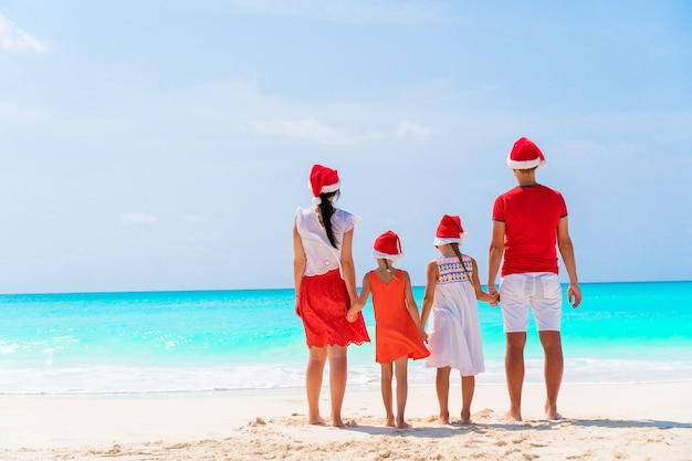 Family of four in red santa hats on a tropical beach celebrating christmas