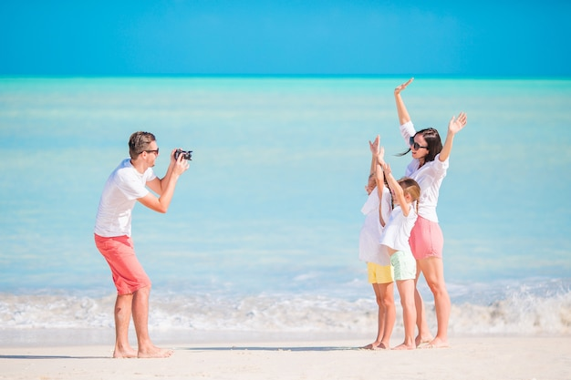 Family of four taking a selfie photo on their beach holidays. family beach vacation