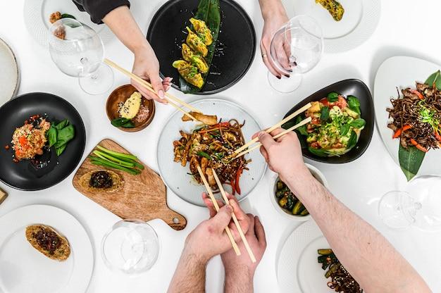 家族、アジア風のフレンドリーなディナー。餃子、春巻き、中華麺、ステーキ、サラダ。お箸で食べる人の手