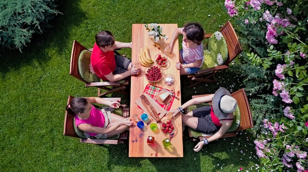 Family and friends eating together outdoors on summer garden party