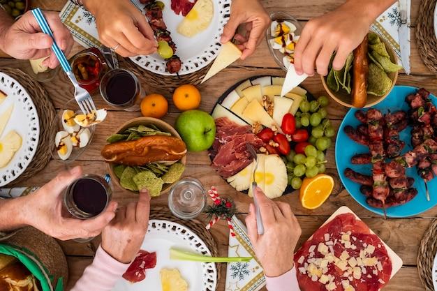 家族の友達は一緒に木製のテーブルで食べ物を食べるのを楽しんでいます