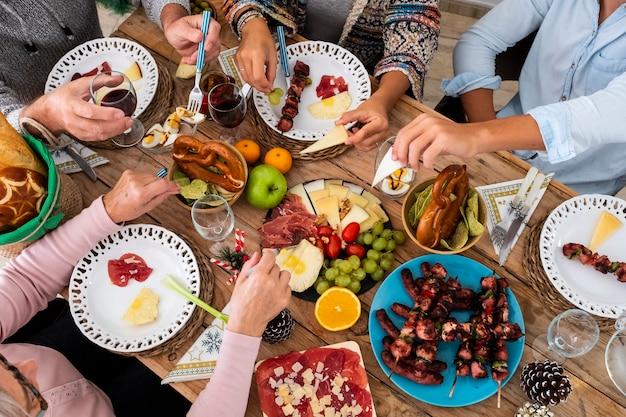 家族の友達は冬に一緒に木製のテーブルで食べ物を食べて楽しんでいます