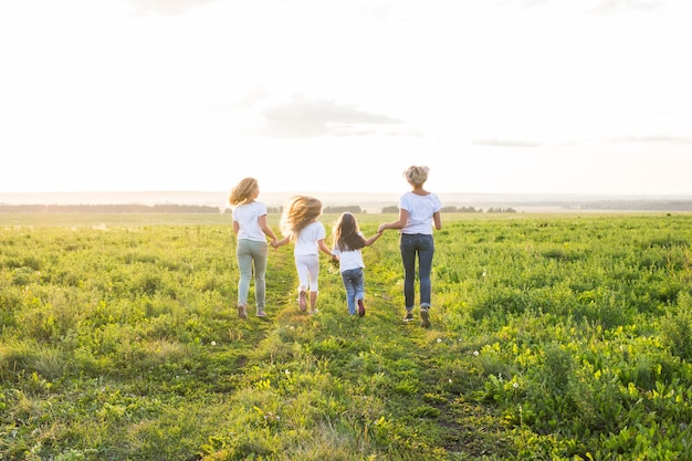 Family, fun and holiday concept - mothers and her daughters going away in green field.