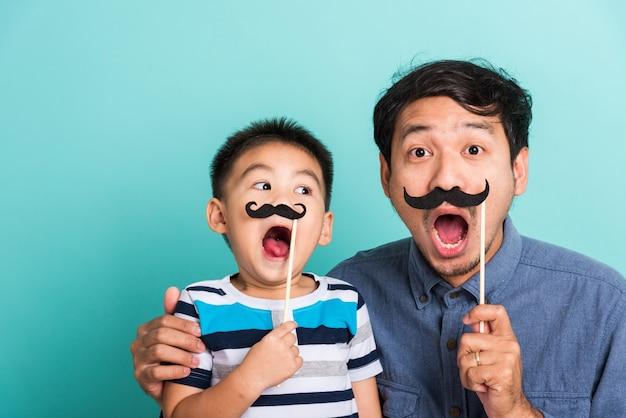 家族の面白い父と彼の息子の子供が写真ブースの近くの顔のために黒い口ひげの小道具を持っています