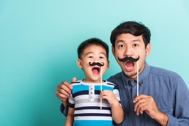 家族の面白い幸せなヒップスターの父と彼の息子は、写真ブースの近くの顔のために黒い口ひげの小道具を保持します