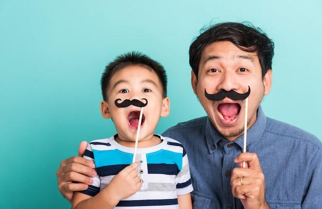 Семья смешной счастливый хипстер отец и его сын ребенок держат черные усы реквизит