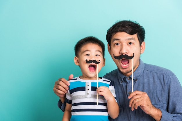 Family funny happy hipster father and his son hold black mustache props for photo booth close face