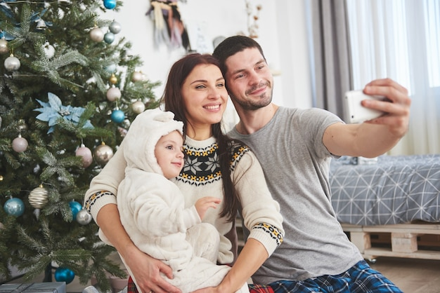 Family gathered around a christmas tree, using a tablet