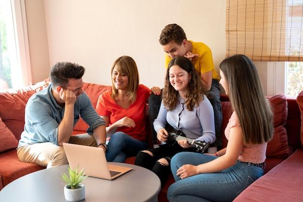 Семья собирается вместе на диване рядом с ноутбуком