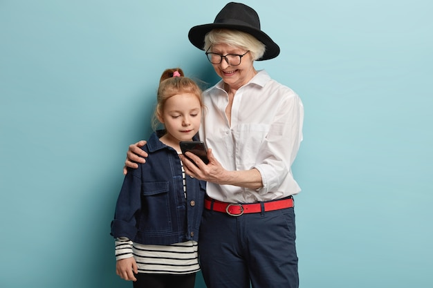 Family, generation and technology concept. happy fashionable grandmother holds smartphone, embraces female grandchild, watch video together, have nice together at home, pose over blue wall