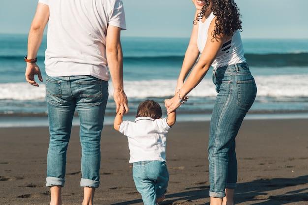 砂浜のビーチで海に行く家族