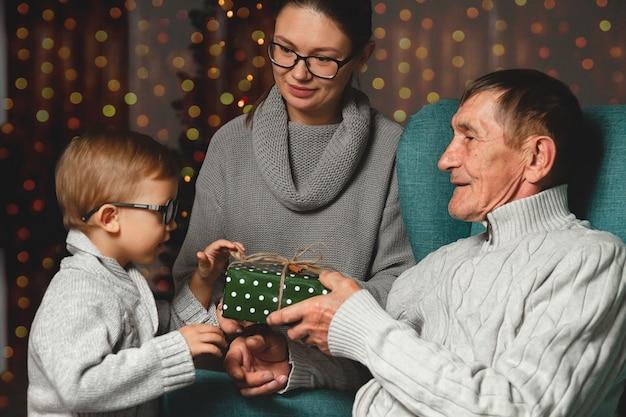 Семейный дедушка, дочь и внук вместе дарят и открывают подарки