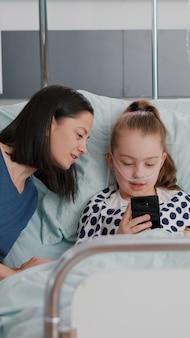 Семья приветствует удаленного друга во время онлайн-видеоконференции с помощью смартфона, отдыхающего в постели после выздоровления. маленький ребенок страдает от хирургической операции в больничной палате