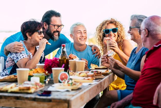 가족 그룹은 음식과 음료가 가득한 테이블과 함께 집에서 야외 우정을 축하하고 함께 즐깁니다.
