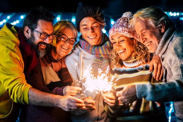 Семейная группа с радостью отмечает канун нового года с огненными бенгальскими огнями.