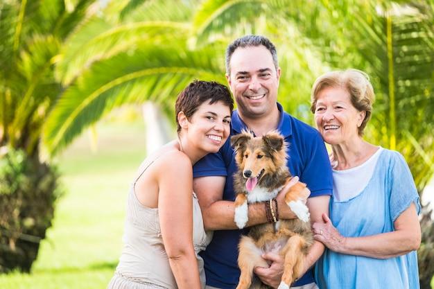 30 세에서 80 세 사이의 다른 연령대를 가진 백인 행복한 사람들의 가족 그룹과 그들과 함께 좋은 재미있는 셰틀 랜드 강아지. 야외 레저 activ에 쾌활한 사람들을위한 사랑과 우정 개념