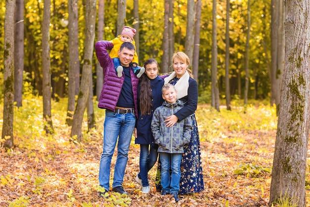 Семейная группа, отдыхая на открытом воздухе в осеннем пейзаже.