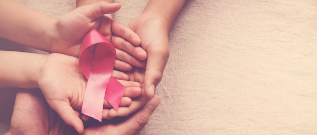 Family hands holding pink ribbon, breast cancer awareness, october pink