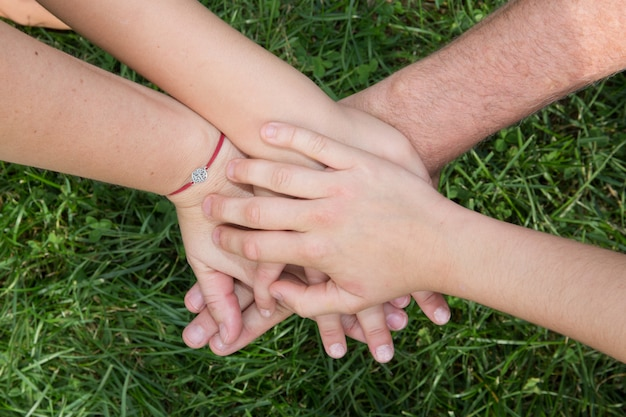 Family hands top each other with grass background