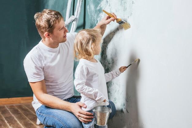 Семья, счастливая дочь с папой делают ремонт дома, красят стены вместе с любовью
