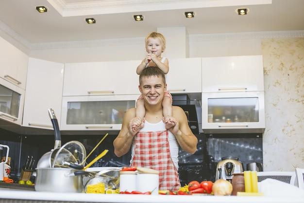 家族、家の台所でお父さんと一緒に笑って、愛を込めて食事を準備する幸せな娘