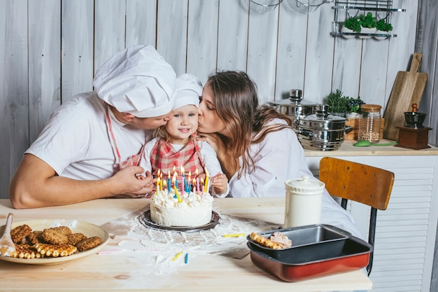 家族、幸せな娘、自宅のキッチンでママとパパと一緒に笑って、バースデーケーキのキャンドルに火をつけた