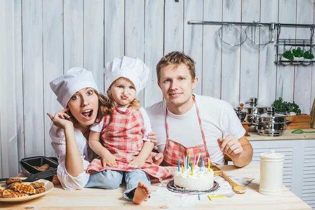 家族、幸せな娘と一緒にキッチンでママとパパと一緒に笑って、愛を込めてバースデーケーキを焼く