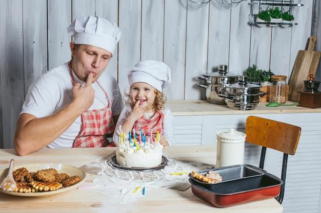 家族、幸せな娘、家で父と一緒に台所で笑って、バースデーケーキのろうそくに火をつけた