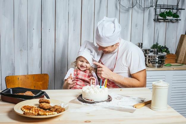 Семья, счастливая дочь с папой дома на кухне смеются и вместе с любовью пекут праздничный торт.