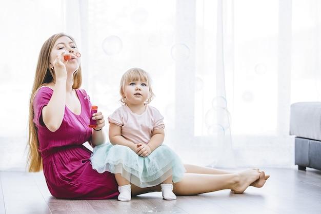 家族の幸せな若い美しいママと娘が一緒に家でシャボン玉を遊んでいます