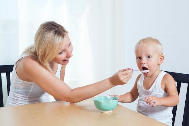Семья завтракает дома. мама кормит ребенка ложкой. мать кормит своего очаровательного ребенка дома. концепция детского питания.