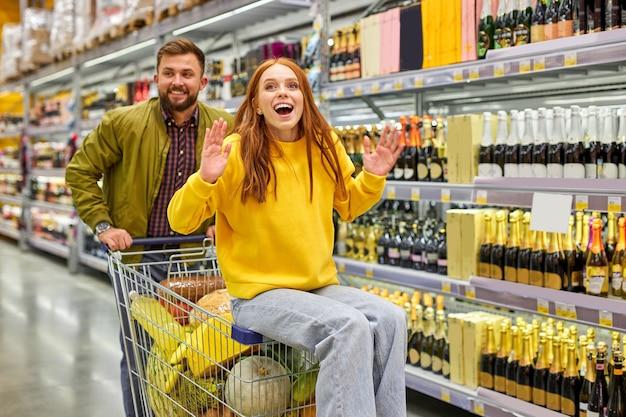 家族は食料品店の通路で楽しんでいます、女性はカートに座って夫と一緒に買い物を楽しんでいます