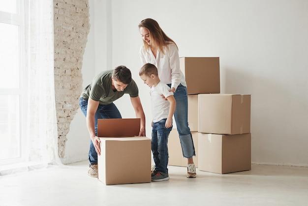 가족이 새 집으로 이사했습니다. 움직이는 상자 포장 풀기.
