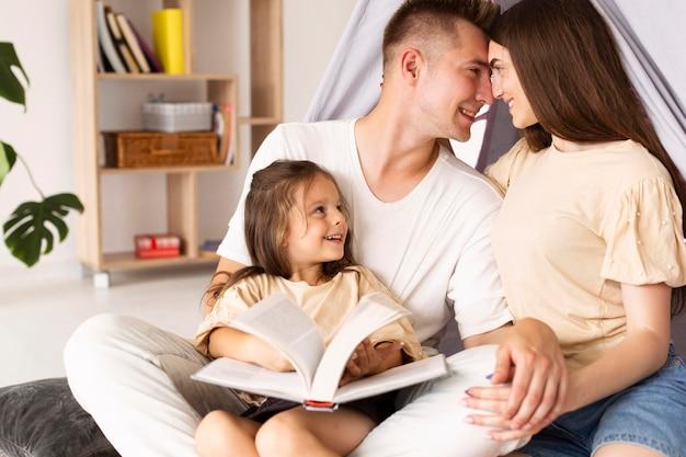 Семья весело проводит время вместе во время чтения