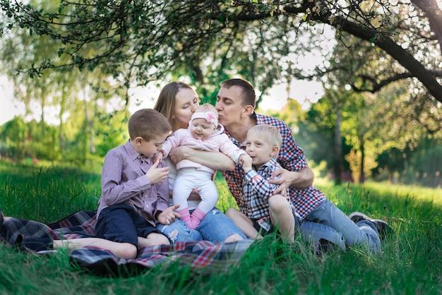 Семья, прекрасно проводящая время на открытом воздухе. мама, папа и трое детей. отец целует дочь