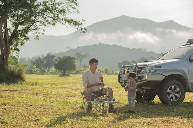 그들의 캠핑카 옆에 피크닉을 갖는 가족. 아버지와 아들의 산에서 일몰 시간에 연주.
