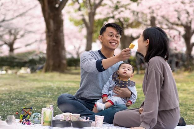 桜の横でピクニックをしている家族