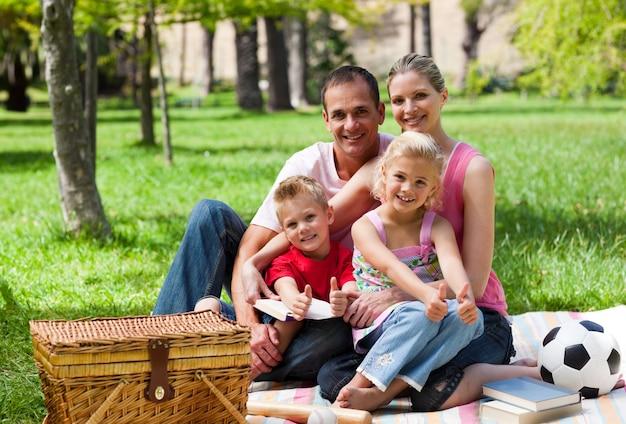 カメラで微笑んだピクニックをしている家族
