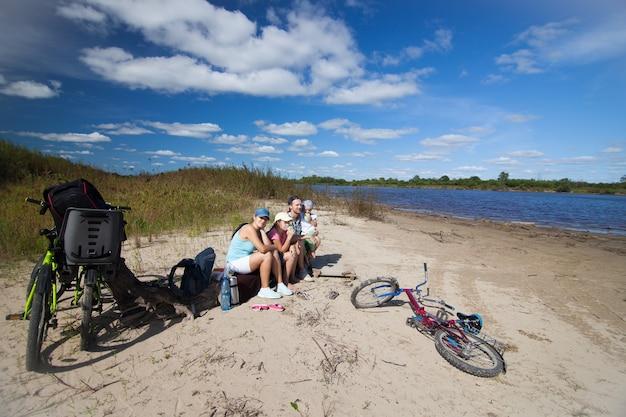 Семья отдыхает на берегу реки со своими велосипедами вокруг
