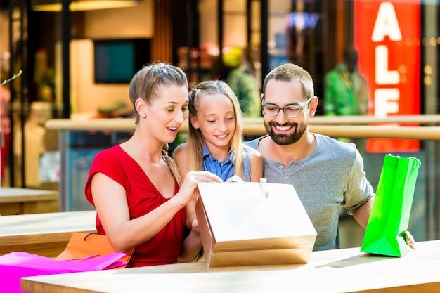 Family having break from shopping in mall