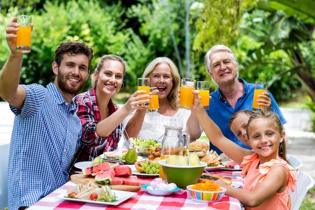 Семья завтракает за столом во дворе