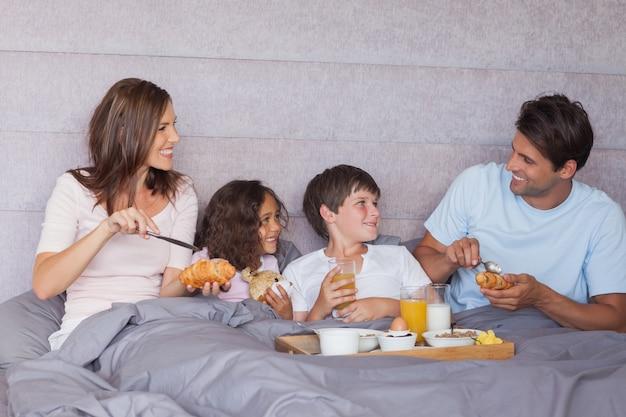 ベッドで朝食をとっている家族
