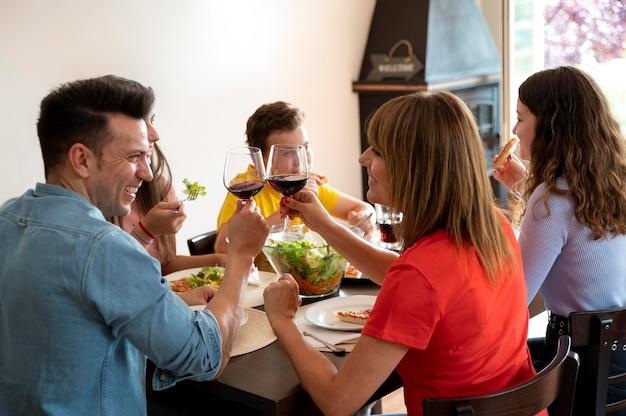 Семья обедает вместе и тосты с бокалами