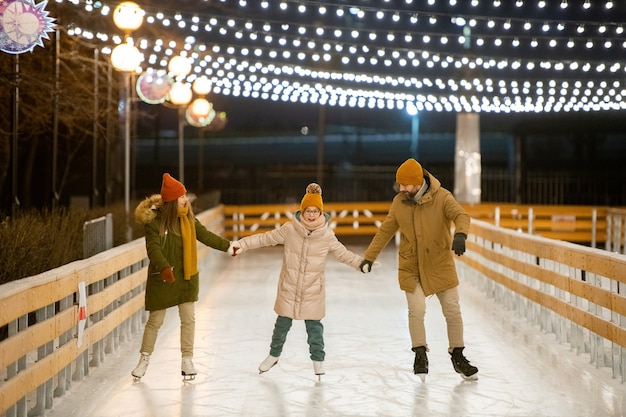 Family having fun on skating rink they teaching their child to skate on figure skates