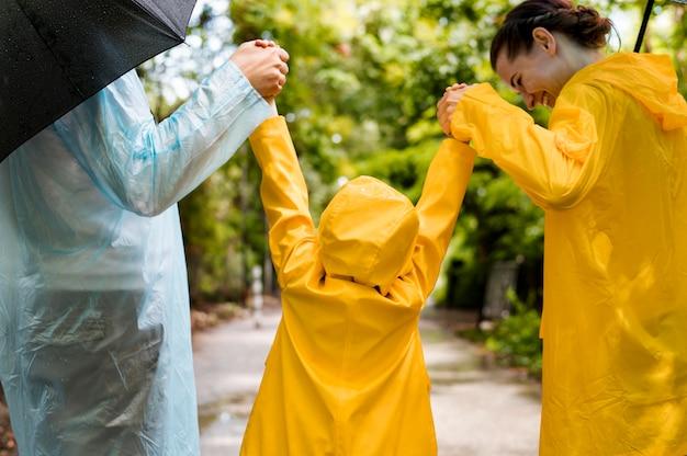 Famiglia divertendosi mentre piove